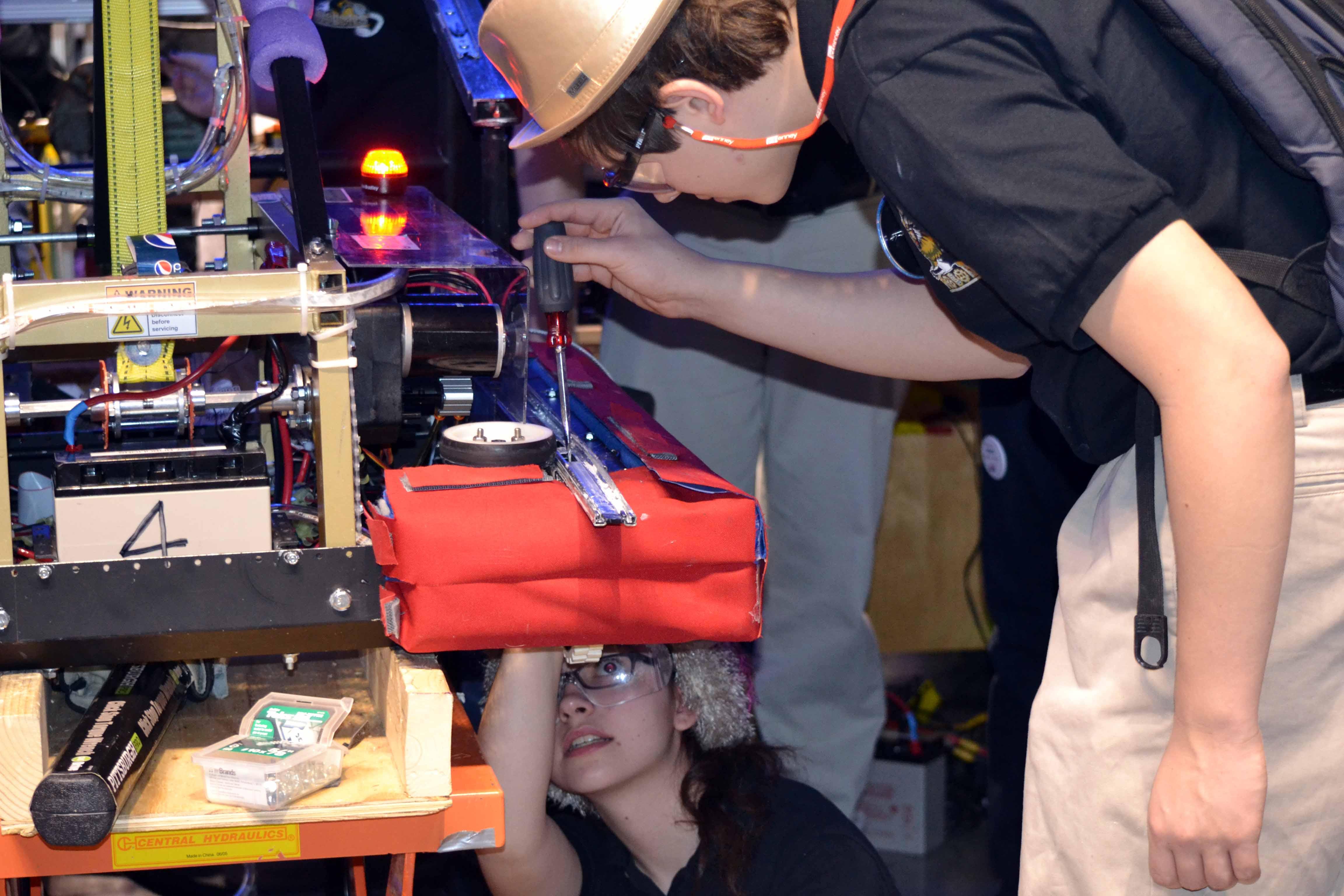 Walter Deitzler, team captain, and Christine Politte, head electrician, work on the robot.