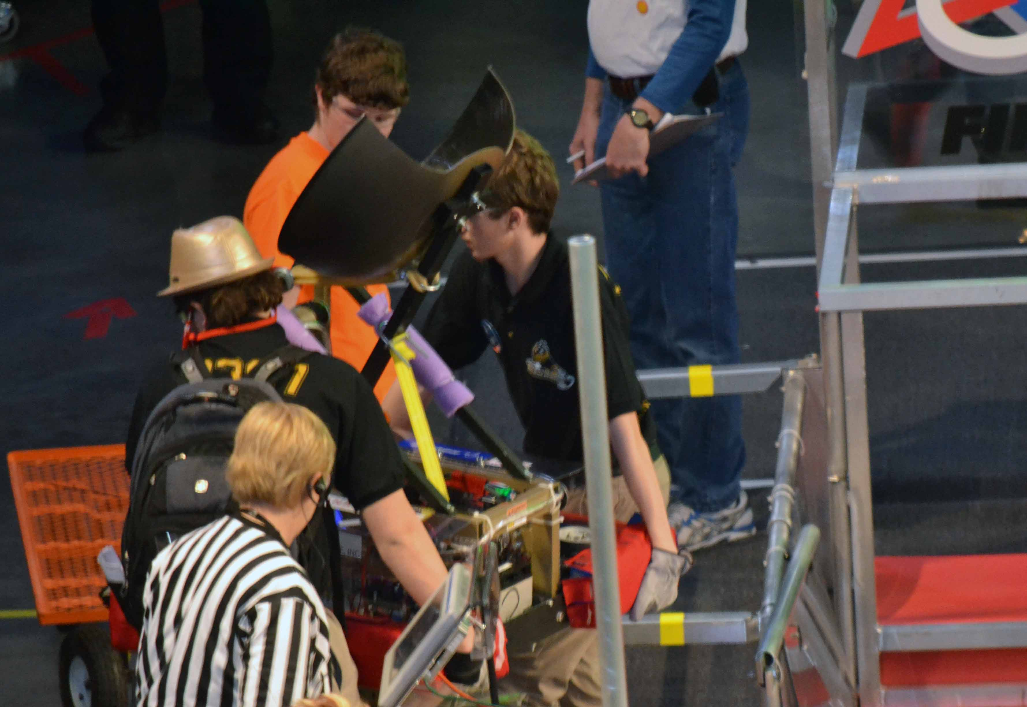 Walter Deitzler and Joshua Stueck remove the robot from the field after a match.