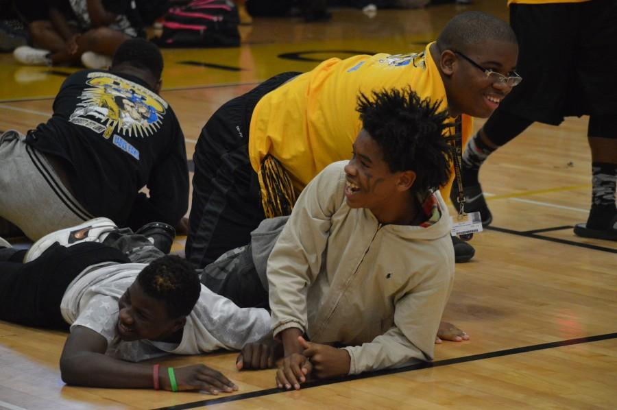 """JV football players Brysom Jones, freshman, Kyron Bailey, freshman, and Jonathan York, sophmore, fall to the floor after going up against the varsity football team in a tug-of-war competetion. """"It was funny because it was our first time going against varsity,"""" said Bailey. """"We knew we were going to lose because they're strong."""""""