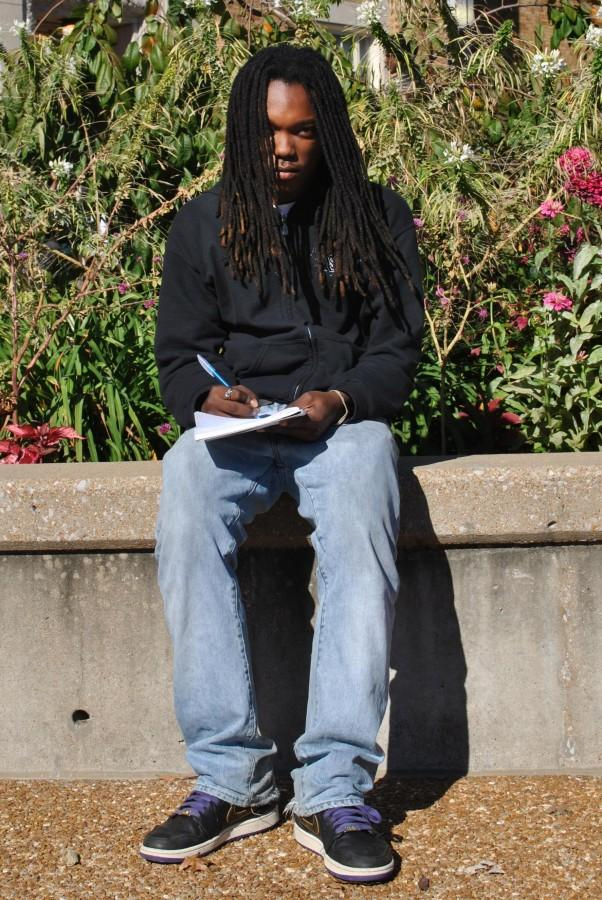 """Fidel Muhammad, senior, brainstorms outside of school while meticulously constructing another song. """"I like writing outside,"""" said Muhammad. """"It helps to see the world I'm talking about in my music."""""""
