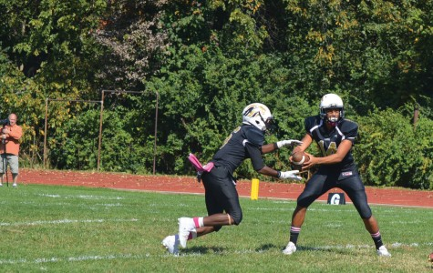 """Darrian Fields, senior running back and cornerback received a handoff from quarterback Keondre Bledsoe. The results of the homecoming game disappointed Fields. """"We didn't finish. We were up by a large lead and we let them come back."""""""