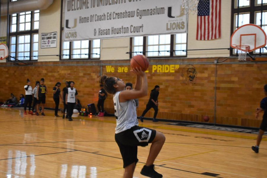 "At practice, Ayanna Williams, junior small forward, goes in for a lay up. ""A jump shot is my favorite shot because it's closer to the basket and easier to score,"" Willams said. "" You are supposed to put your all into the shot."""