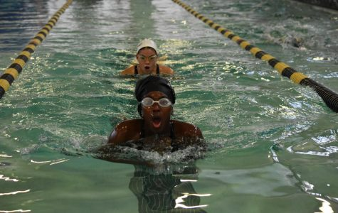 """At swim practice, Chloe Easter and Nicole Kellogg, seniors, finish a lap of breast stroke.""""When I'm swimming, I think of the most random things like old TV show clips, what I want for dinner or what's the person next to me doing,"""" Easter said."""