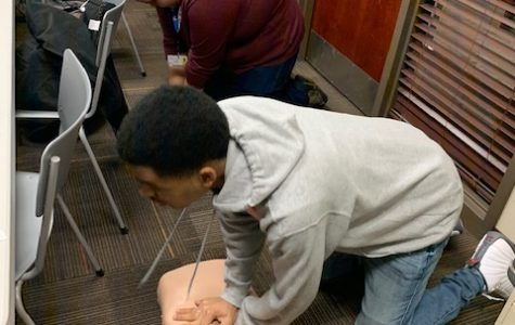 "At their first session, Christian Hollloway and Timothy Dailey, seniors, perform CPR on a dummy as part of their physical test to complete their CPR certification. ""So far it's been super exciting just based on the things we've been told we will do and the responsibility we will have,"" Dailey said."