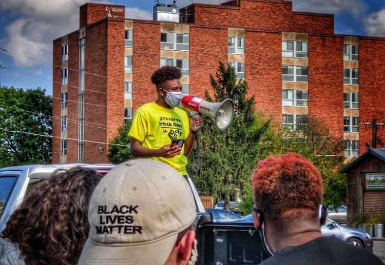 "Megaphone in hand, Michael Simmons, sophomore, delivers a speech to protesters before setting off to march through U. City. ""It was very important to me that I made sure my voice was heard,"" Simmons said. Simmons was one of the main leaders who helped to organize the protest."