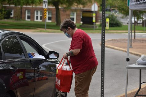 Peggy Halter, English teacher, hands out books  to students in her literature classes during a drive-through school supply pickup in September.