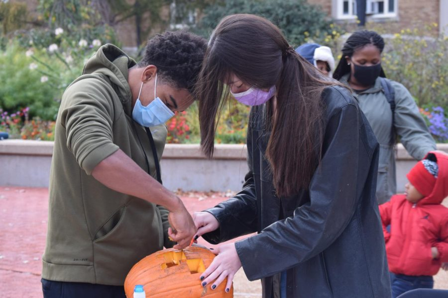 During the afternoon carving session, Cameron Martin (left) and Maxine Adams (right), juniors, work together to carve a pumpkin for the evening's events.