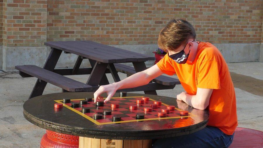 Adam Holahan, senior, sets up a checkers board.