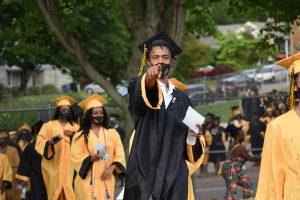 Brandon Ming, points at camera while walking up into graduation